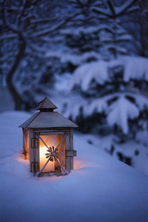 close up of glowing lantern in snow photograph by cultura