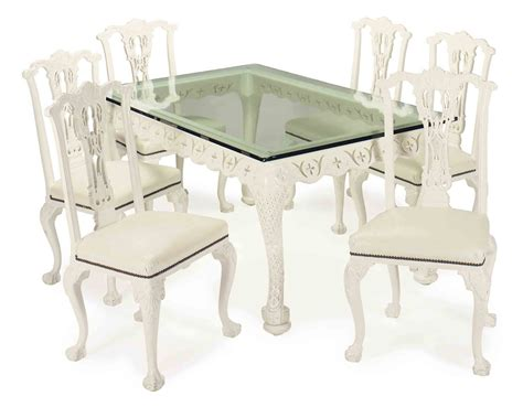 a contemporary white painted glass top dining table and