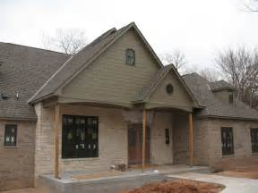 Beige brick yellow beige stone a gray brown roof and sage green