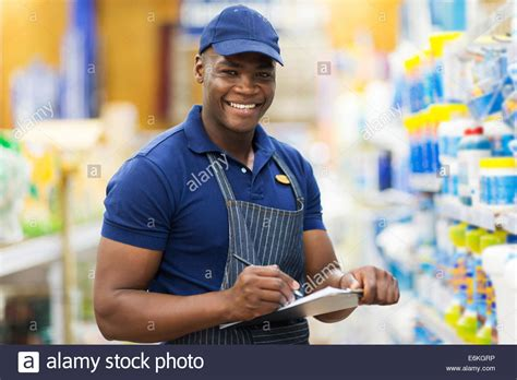 happy shop assistant checking stock in supermarket