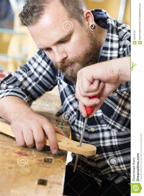 working man tattoo up of craftsman files wooden guitar neck in workshop