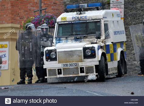 land rover psni psni officers beside an armoured land rover during riots