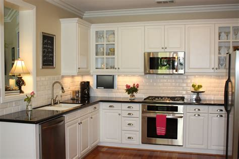 Rectangle Cream Tile Back Splash Combined With L Shape White Kitchen Cabinets With Black Countertops