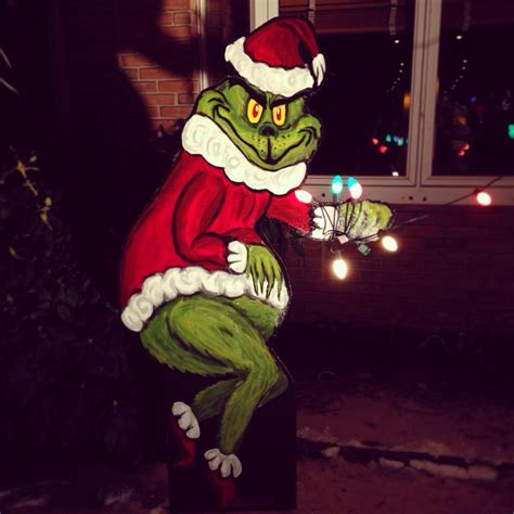 grinch stealing christmas decoration lights from house