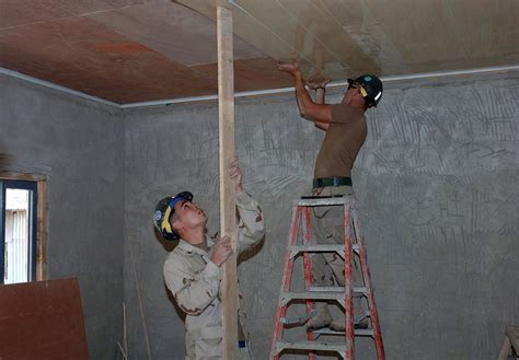 Putting Up Ceiling Tiles by File Us Navy 071004 N 1003p 001 Utilitiesman 3rd Class Brian Sievers Left Holds A Four By Four