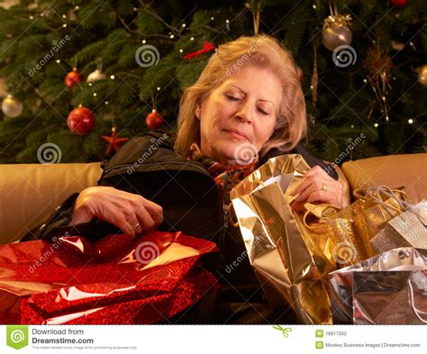 senior woman returning after christmas shopp stock