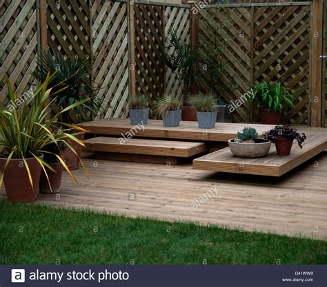 Garden Trellis For Pots Plants In Pots On Low Wooden Table On Wooden Decking In