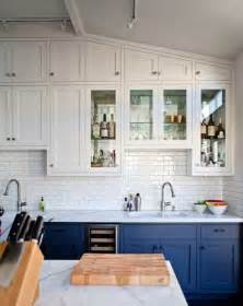 Cabinets and backsplash are grounded by deep blue bottom cabinets