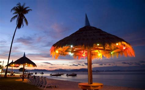 malaysia night beach hut wooden umbrellas straw romantic