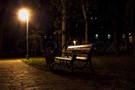 bench at night night view of park bench and street lantern stock photo