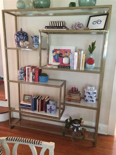 handmade gold bookshelf with glass shelving by five fork