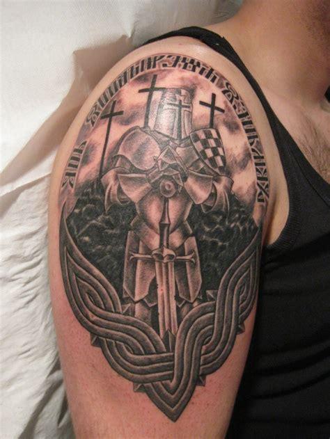 gepanzerter krieger mit schwert und kreuz tattoo an der