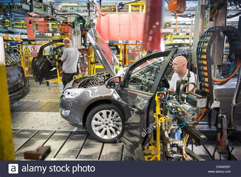 car factory car assembly workers fitting doors to cars on production