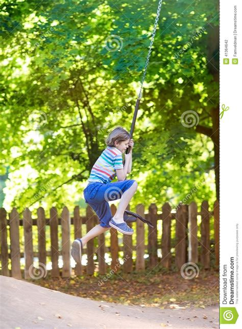 swing swing swing on a summer day funny little boy enjoying swing ride on a playground stock