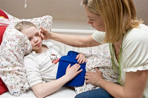 how to comfort a sick child a mother comforting her sick daughter stock photo