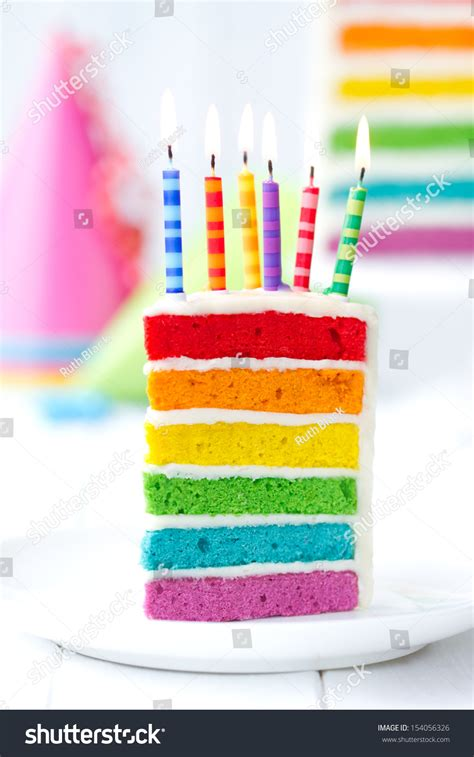rainbow cake and cupcakes decorated with birthday candles rainbow cake decorated with birthday candles stock photo 154056326