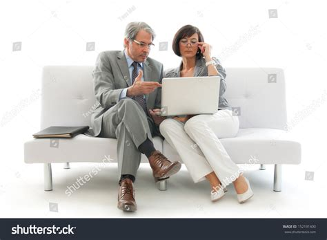 people sitting on a couch two business people sitting working together stock photo