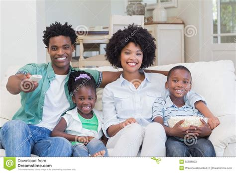 family watching tv with popcorn in living room stock photo happy family watching television eating popcorn stock