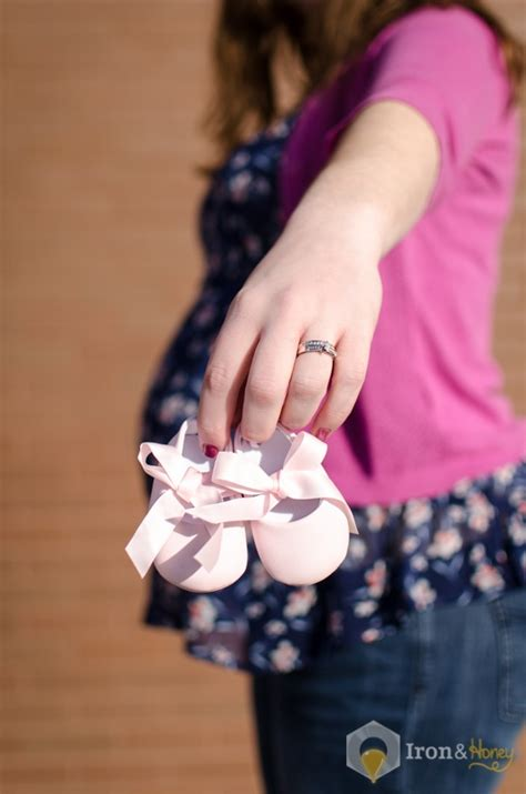 holding baby shoes showing wedding ring with