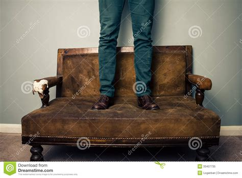 standing on the couch man wearing shoes standing on sofa royalty free stock