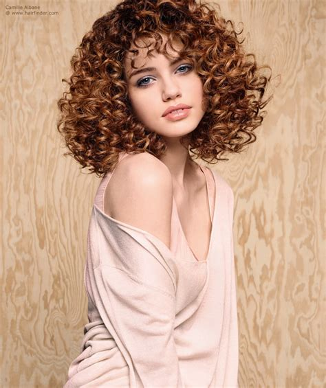 perm mid length hair on lady over 50 medium length hairstyle with spirals that twirl around the