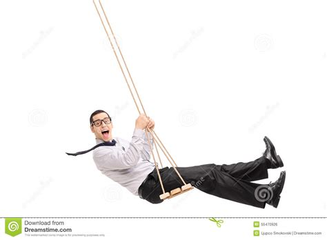 swinging man delighted young man swinging on a swing stock photo