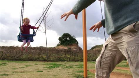 pushing a swing father pushing daughter on swing stock footage video