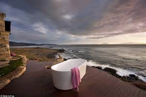 At one with nature in your outdoor bath the ocean rumbles against the