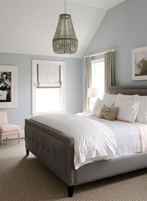gorgeous bedroom with blue walls paint color gray linen tufted bed crisp white bedding pink