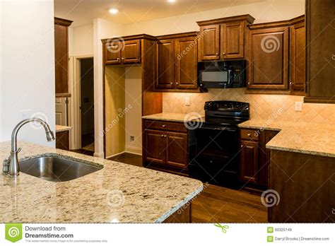 black kitchen cabinets with stainless steel appliances stainless steel sink and black appliances stock image