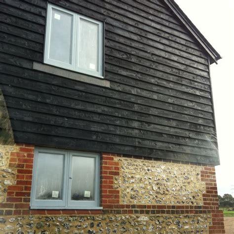 Black Shiplap Cladding Black Barn Board Cladding With Brick And Flint And Grey