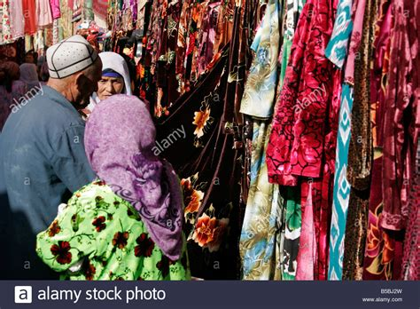 uzbek women selling traditional wedding skullcaps and dresses sunday old uzbek man with his wife shopping on sunday market in