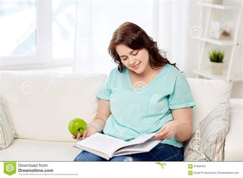 plus size with book and apple at home stock photo