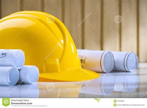 yellow rolls yellow helmet and rolls of blueprints on stock
