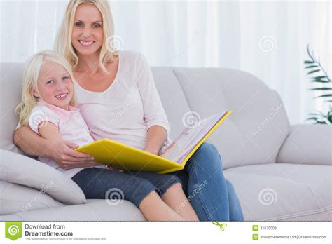 mom on sofa mother and daughter sitting on couch reading a book stock