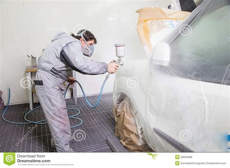 spray painter labourer car painter spraying paint on bodywork parts royalty