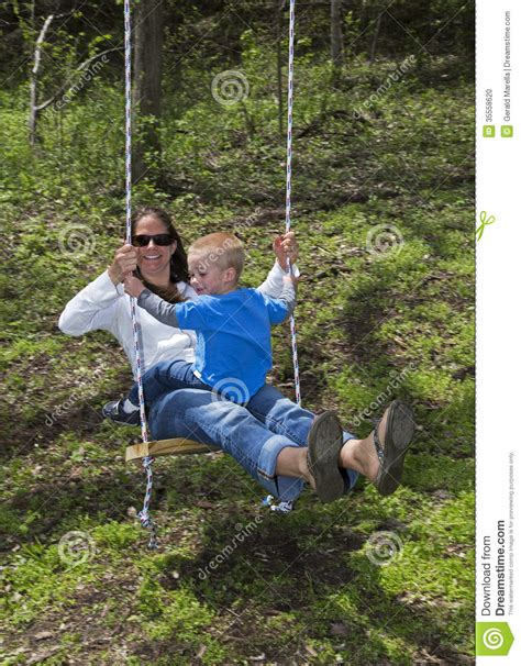 swing her young mother and son playing on a swing stock photo