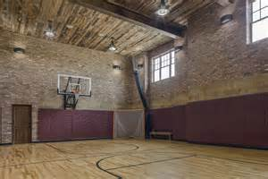 Dazzling indoor basketball hoop in home gym farmhouse with flooring next to basketball court in