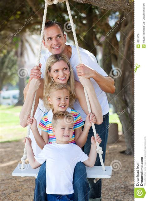 family swing family playing together with a swing royalty free stock
