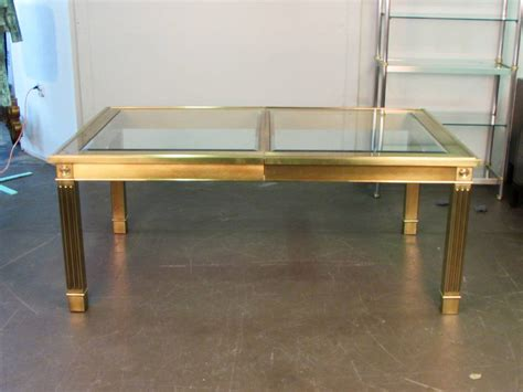 striking brass and glass dining table with leaf by