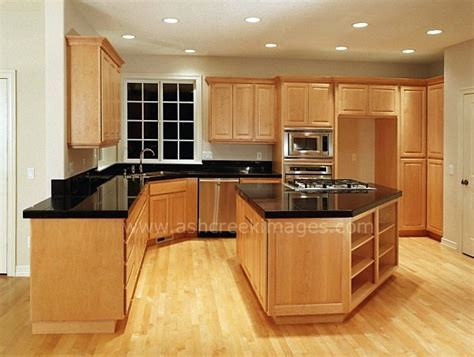 light wood kitchen cabinets with black countertops black counter tops and wood floors with the light