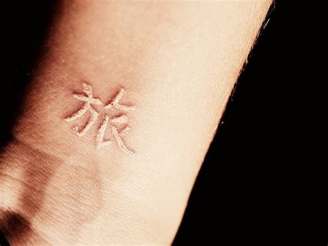white ink chinese hieroglyph tattoo on wrist