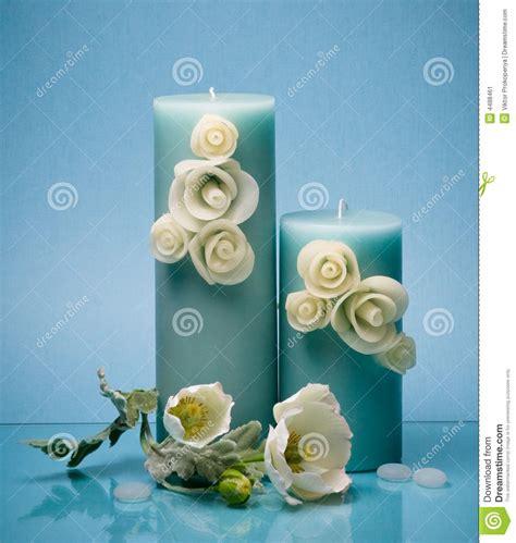 candele eleganti due candele eleganti e fiori decorativi sull azzurro