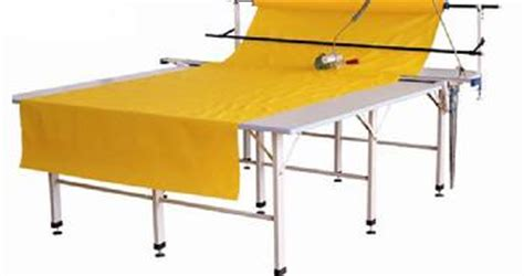 commercial fabric cutting table end cutting system includes table roll rack with bar cones