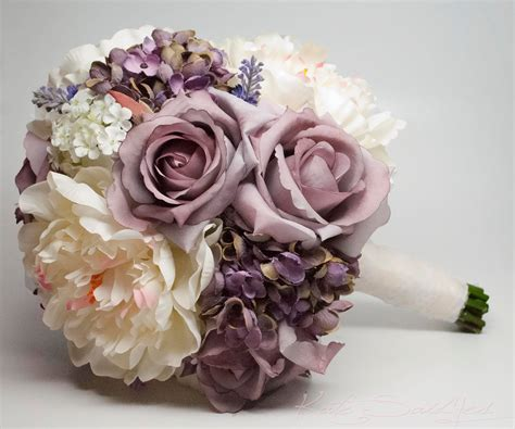 a shabby chic bouquet with lavender roses and hydrangea as well as ivory peonies and lace from
