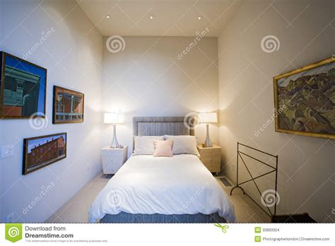 picture for bedroom lit ls by bed with frames on wall in bedroom stock