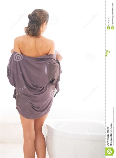 undressing bathroom young woman undressing in bathroom rear view stock photo