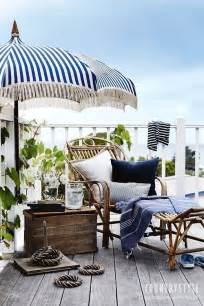 Blue And White Striped Patio Umbrella A Navy And White Striped Umbrella Rattan Chaise Wooden Chest Porches And Outdoor Spaces