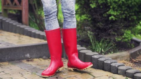 wearing rubber boots on pavement and wearing boots stock