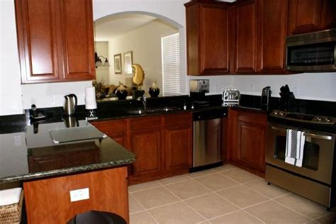 cherry wood kitchen cabinets with black granite cherry